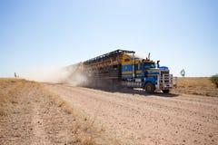 Dwoistego pokładu bydła drogowy pociąg zbliża się na zakurzonej odludzie drodze Obrazy Stock