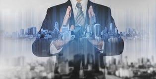Dwoistego ujawnienia biznesmen trzyma błękitnego miasto hologram, nieruchomość biznesu technologia Obrazy Stock