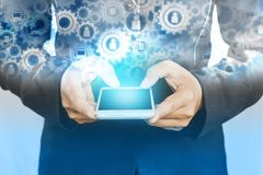 Dwoistego ujawnienia biznesowego mężczyzna ręka trzyma mądrze telefon z cogwheel technologia internet i położenie obrazy stock