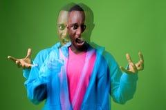 Dwoistego ujawnienia strzał młody Afrykański mężczyzna przeciw zielonemu tłu zdjęcia royalty free