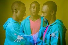 Dwoistego ujawnienia strzał młody Afrykański mężczyzna przeciw zielonemu tłu zdjęcia stock