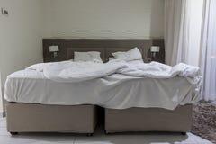 Dwoisty łóżko w pokoju hotelowym z bałaganiącym łóżkiem Fotografia Royalty Free