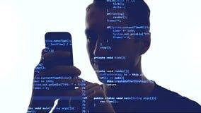 Dwoisty ujawnienie hacker u?ywa smartphone z b??kitnym kodem na on Dwoista ekspozycja m??czyzny programista u?ywa m?drze telefon zbiory wideo