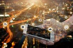 Dwoisty ujawnienie ręka chwyta smartphone nad nocy miastem zdjęcia stock