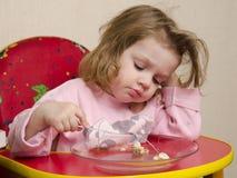 Dwuletnia dziewczyna je z rozwidleniem przy stołem w kuchni Obraz Royalty Free