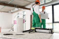 Dye tin with plug-driving gun in apartment. Close up big bank with paint and power-actuated fastening tool locating in room Royalty Free Stock Image
