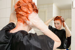 Dye your hair. Caucasian woman with short hair dying her hair red in front of mirror in her own bathroom Royalty Free Stock Photography