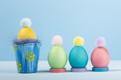 Dyed bright Easter eggs in the nest and in stands with colorful pompons. On a blue background stock photography