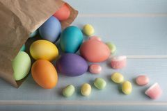 Dyed Easter  chicken eggs with lollipops. Mix of Easter colorful dyed chicken eggs in a paper bag and sweets on a blue wooden table royalty free stock images
