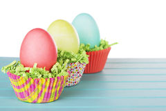 Dyed Easter eggs in a nest of green grass confetti and cup cake Stock Image