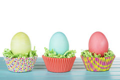 Dyed Easter eggs in a nest of green grass confetti and cup cake Royalty Free Stock Image