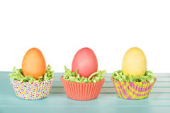 Dyed Easter eggs in a nest of green grass confetti and cup cake Royalty Free Stock Images