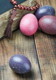 Dyed Easter eggs and religious Christian symbols. On a wooden table royalty free stock photo