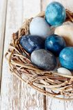 Dyed Easter vintage eggs with scuffs on a light gray background in a wicker basket. Stylish Background with easter eggs, modern. Happy Easter card stock photos