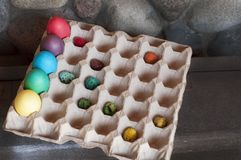 A dyed eggs in a packing for eggs. A dyed big and small eggs in a packing for eggs stock images