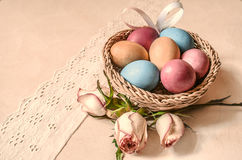 Colored eggs with rose buds and satin bow in a wattled basket Stock Photo