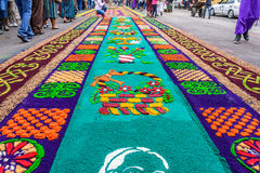 Dyed sawdust Lent carpets, Antigua, Guatemala. Antigua, Guatemala -  March 13, 2016: Locals walk past handmade dyed sawdust Lent carpets for procession in Stock Image