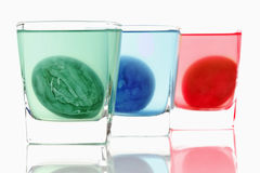 Dyeing of Easter eggs in glasses Stock Photo