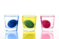 Dyeing of Easter eggs in glasses Stock Photos