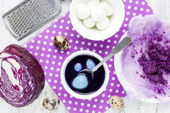 Dyeing Easter eggs with natural dye colors - red cabbage blue Ea Royalty Free Stock Photography