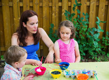 Dyeing Easter Eggs Outside with Mom Royalty Free Stock Photos