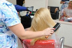 After dyeing hair, the hairdresser washes the girl`s hair and wa royalty free stock photo
