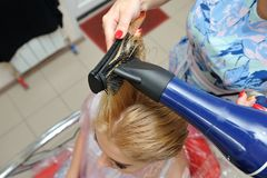 After dyeing hair, the hairdresser washes the girl`s hair and wa stock photos