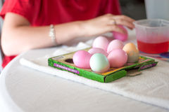 Dying Easter Eggs. A girl dyes Easter Eggs at a table Royalty Free Stock Photography