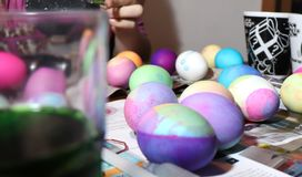 Dying Easter eggs at a kitchen table stock photos