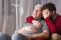 Dying father and despair son. Last farewell - dying father and despair son Stock Photo