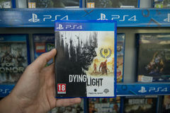 Dying Light. Bratislava, Slovakia, circa april 2017: Man holding Dying Light videogame on Sony Playstation 4 console in store Royalty Free Stock Images