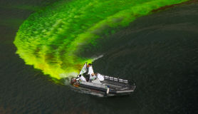 Dying the River for St. Patrick's Day. A picture of the boat dispersing orange dye to turn the Chicago River emerald green for St. Patrick's Day. The boat is in royalty free stock image