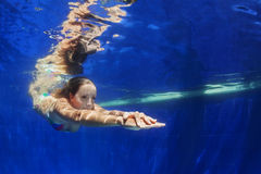 Dyk för ung kvinna som är undervattens- i blå simbassäng royaltyfria bilder