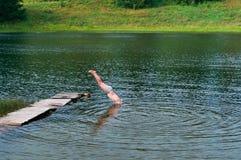 Dyka från pirhuvudet ner, hoppet in i vattnet royaltyfri bild