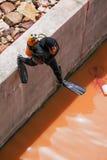 Dykare dyker in för att kontrollera sprickor av byggnader under vatten Arkivfoton