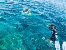 Dykare i vattentäta dräkter för svart dykning med aluminum kanistrar för skinande metall svävar, fördjupar i blått havsvatten på  fotografering för bildbyråer