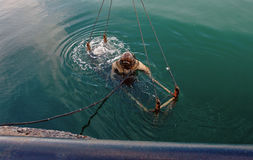 Dykaren i tung spacesuit kasta sig in i havet Royaltyfri Foto