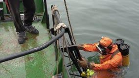 Dykaren tar ljust, videokameran för undervattens- skytte och dyk in i havet arkivfilmer