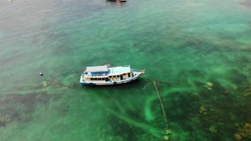 Dykfartyg med utrustning i havet Motordykfartyg med utrustning och behållare som svävar på blått havsvatten nära Koh Tao lager videofilmer