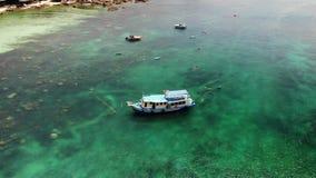 Dykfartyg med utrustning i havet Motordykfartyg med utrustning och behållare som svävar på blått havsvatten nära Koh Tao arkivfilmer