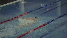 Dykning för sportkvinnasimmare i klart vatten i tom simbassängultrarapid lager videofilmer