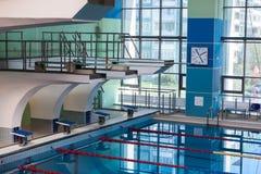 Dykningbräden in i vatten i simbassängen Arkivfoton