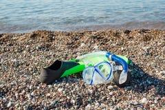 Dykningmaskering, snorkel och fenor på en strand Arkivfoton