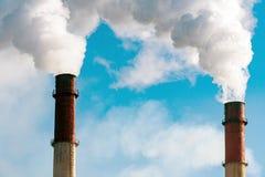 Dym od fabryk drymb przeciw niebieskiemu niebu Obrazy Stock