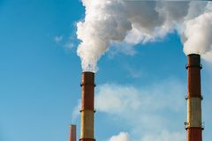 Dym od fabryk drymb przeciw niebieskiemu niebu Fotografia Stock