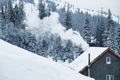 Dym od kominu dom na ośrodku narciarskim w zimie fotografia stock