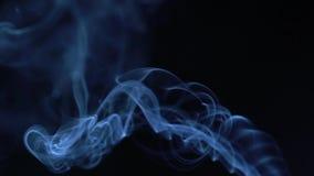 Dymi wolno unosić się przez przestrzeni przeciw czarnemu tłu 240 fps zwolnione tempo zdjęcie wideo