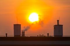 Dymienie kominy przy zima wschodem słońca Obrazy Stock