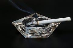 Dymienie papieros w krystalicznym ashtray zdjęcia stock