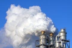 Dymne chmury od kominu przeciw niebieskiemu niebu Fotografia Stock